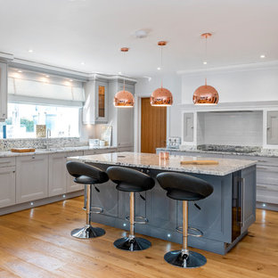 Large traditional kitchen in Other with recessed-panel cabinets, grey cabinets, marble worktops, white splashback, metro tiled splashback, an island, grey worktops and medium hardwood flooring.