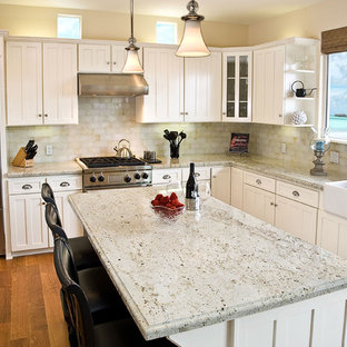 Photo of a mid-sized traditional u-shaped kitchen in Orange County with stainless steel appliances, a farmhouse sink, shaker cabinets, white cabinets, granite benchtops, light hardwood floors and with island.