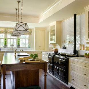 ボストンのヴィクトリアン調のおしゃれなアイランドキッチン (エプロンフロントシンク、落し込みパネル扉のキャビネット、黄色いキャビネット、大理石カウンター、白いキッチンパネル、サブウェイタイルのキッチンパネル、黒い調理設備、濃色無垢フローリング) の写真