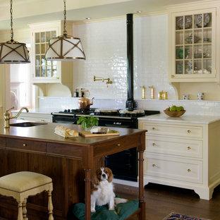 ボストンのヴィクトリアン調のおしゃれなアイランドキッチン (黄色いキャビネット、大理石カウンター、白いキッチンパネル、サブウェイタイルのキッチンパネル、黒い調理設備、濃色無垢フローリング、シングルシンク、ガラス扉のキャビネット) の写真