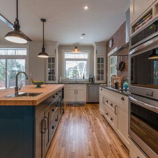 Bild på ett industriellt kök, med en undermonterad diskho, skåp i shakerstil, blå skåp, träbänkskiva, rött stänkskydd, stänkskydd i terrakottakakel, rostfria vitvaror, ljust trägolv och en köksö