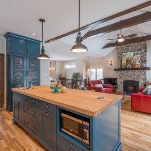 Ejemplo de cocina industrial con fregadero bajoencimera, armarios estilo shaker, puertas de armario azules, encimera de madera, salpicadero rojo, salpicadero de azulejos de terracota, electrodomésticos de acero inoxidable, suelo de madera clara y una isla