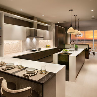 This is an example of a large contemporary u-shaped eat-in kitchen in Miami with an undermount sink, flat-panel cabinets, dark wood cabinets, white splashback, panelled appliances, multiple islands, quartzite benchtops, ceramic splashback and limestone floors.