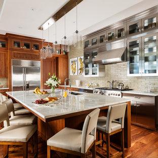 他の地域のコンテンポラリースタイルのおしゃれなキッチン (アンダーカウンターシンク、ガラス扉のキャビネット、ステンレスキャビネット、ベージュキッチンパネル、サブウェイタイルのキッチンパネル、シルバーの調理設備の、無垢フローリング、茶色い床、ベージュのキッチンカウンター) の写真