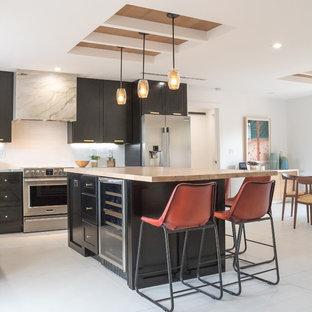 Foto de cocina comedor costera, de tamaño medio, con puertas de armario negras, salpicadero blanco, electrodomésticos de acero inoxidable, una isla, suelo blanco, suelo de baldosas de porcelana y armarios estilo shaker