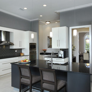 Inspiration for a mid-sized contemporary u-shaped kitchen in Miami with stainless steel appliances, a farmhouse sink, flat-panel cabinets, white cabinets, granite benchtops, black splashback, subway tile splashback, porcelain floors and with island.
