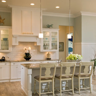 Mid-sized traditional eat-in kitchen inspiration - Example of a mid-sized classic l-shaped light wood floor eat-in kitchen design in Miami with glass-front cabinets, white cabinets, white backsplash, an island, granite countertops, subway tile backsplash and stainless steel appliances