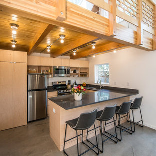 Inspiration for a mid-sized modern l-shaped concrete floor and gray floor open concept kitchen remodel in Portland with an undermount sink, flat-panel cabinets, light wood cabinets, white backsplash, stainless steel appliances, a peninsula, gray countertops and solid surface countertops