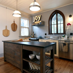 Inspiration for a small eclectic single-wall open plan kitchen in Portland with an integrated sink, shaker cabinets, white cabinets, stainless steel benchtops, grey splashback, ceramic splashback, stainless steel appliances and medium hardwood floors.