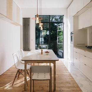 Design ideas for a scandinavian single-wall kitchen/diner in London with flat-panel cabinets, white cabinets, wood worktops and medium hardwood flooring.