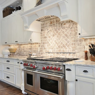 Large farmhouse enclosed kitchen pictures - Large cottage u-shaped dark wood floor enclosed kitchen photo in Atlanta with a farmhouse sink, recessed-panel cabinets, white cabinets, quartz countertops, multicolored backsplash, stone tile backsplash, stainless steel appliances and an island