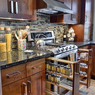 アトランタのトラディショナルスタイルのおしゃれなキッチン (シェーカースタイル扉のキャビネット、濃色木目調キャビネット、マルチカラーのキッチンパネル、シルバーの調理設備の、黒いキッチンカウンター) の写真