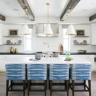 Maritime Küche in U-Form mit Landhausspüle, Schrankfronten im Shaker-Stil, weißen Schränken, Küchenrückwand in Weiß, Küchengeräten aus Edelstahl, braunem Holzboden und Kücheninsel in Orange County