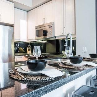 トロントの中サイズのラスティックスタイルのおしゃれなキッチン (アンダーカウンターシンク、シェーカースタイル扉のキャビネット、ベージュのキャビネット、珪岩カウンター、黒いキッチンパネル、石スラブのキッチンパネル、シルバーの調理設備の、リノリウムの床、茶色い床、黒いキッチンカウンター) の写真