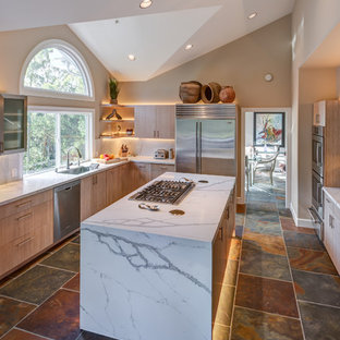 This is an example of a mid-sized contemporary l-shaped separate kitchen in San Francisco with flat-panel cabinets, quartz benchtops, stainless steel appliances, porcelain floors, with island, an undermount sink, light wood cabinets, multi-coloured splashback and slate splashback.