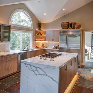This is an example of a mid-sized contemporary l-shaped open plan kitchen in San Francisco with flat-panel cabinets, quartz benchtops, stainless steel appliances, with island, an undermount sink, light wood cabinets, slate floors, multi-coloured splashback and slate splashback.