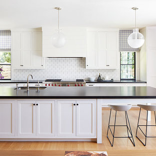 This is an example of a large classic galley open plan kitchen in San Francisco with a submerged sink, white cabinets, white splashback, metro tiled splashback, stainless steel appliances, light hardwood flooring, an island, shaker cabinets, beige floors, composite countertops and black worktops.