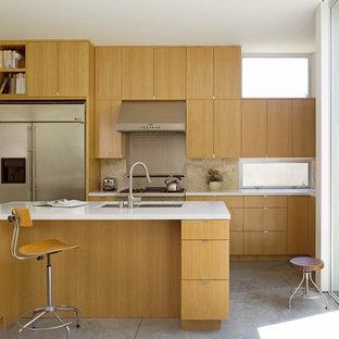 ロサンゼルスの中サイズのモダンスタイルのおしゃれなキッチン (アンダーカウンターシンク、フラットパネル扉のキャビネット、中間色木目調キャビネット、クオーツストーンカウンター、石タイルのキッチンパネル、シルバーの調理設備の、コンクリートの床、ベージュキッチンパネル、グレーの床) の写真