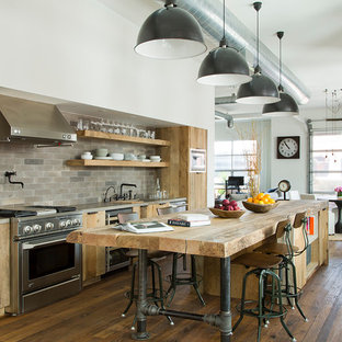 Large industrial open concept kitchen pictures - Large urban galley dark wood floor open concept kitchen photo in Los Angeles with flat-panel cabinets, an island, wood countertops, gray backsplash, stainless steel appliances and light wood cabinets