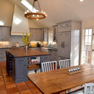 This is an example of a transitional l-shaped open plan kitchen in Denver with a farmhouse sink, recessed-panel cabinets, grey cabinets, wood benchtops, grey splashback, glass tile splashback, panelled appliances, terra-cotta floors and with island.