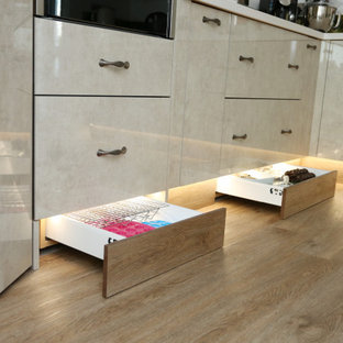 Inspiration for a mid-sized eclectic l-shaped separate kitchen in Other with an integrated sink, flat-panel cabinets, beige cabinets, solid surface benchtops, multi-coloured splashback, glass sheet splashback, black appliances, with island and white benchtop.