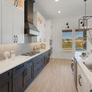 ジャクソンビルの広いインダストリアルスタイルのおしゃれなキッチン (シングルシンク、シェーカースタイル扉のキャビネット、白いキャビネット、クオーツストーンカウンター、黒いキッチンパネル、磁器タイルのキッチンパネル、シルバーの調理設備、クッションフロア、グレーの床、白いキッチンカウンター) の写真