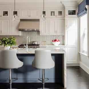 Ispirazione per una grande cucina chic con lavello sottopiano, ante a filo, ante beige, top in marmo, paraspruzzi grigio, paraspruzzi con piastrelle di vetro, elettrodomestici in acciaio inossidabile, parquet scuro, isola, pavimento marrone e top bianco