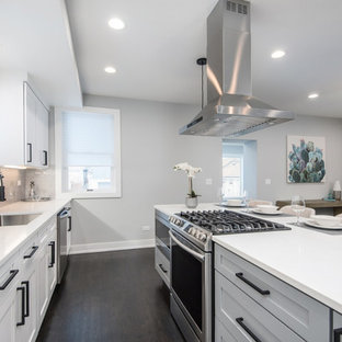 Mid-sized contemporary eat-in kitchen ideas - Inspiration for a mid-sized contemporary single-wall dark wood floor and brown floor eat-in kitchen remodel in Chicago with an undermount sink, shaker cabinets, white cabinets, quartz countertops, gray backsplash, ceramic backsplash, stainless steel appliances, an island and white countertops