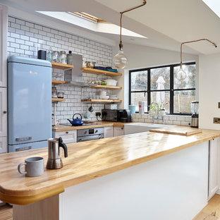 Kleine Country Küche in U-Form mit Landhausspüle, Schrankfronten mit vertiefter Füllung, weißen Schränken, Arbeitsplatte aus Holz, Küchenrückwand in Weiß, Rückwand aus Metrofliesen, bunten Elektrogeräten, hellem Holzboden und Halbinsel in London