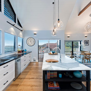 Inspiration for a beach style galley open plan kitchen in Sydney with a double-bowl sink, shaker cabinets, white cabinets, wood benchtops, white splashback, stainless steel appliances, light hardwood floors and an island.