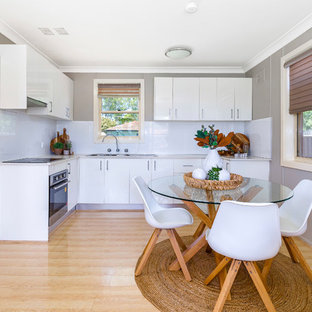 This is an example of a transitional l-shaped eat-in kitchen in Sydney with a double-bowl sink, flat-panel cabinets, white cabinets, white splashback, black appliances, light hardwood floors, beige floor and beige benchtop.