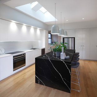 Design ideas for a contemporary l-shaped kitchen in Sydney with quartz benchtops, with island, an undermount sink, stainless steel appliances, light hardwood floors and beige floor.