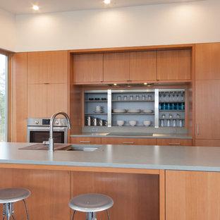 Inspiration pour une grand cuisine américaine linéaire minimaliste avec un évier 1 bac, un placard à porte plane, des portes de placard en bois brun, un plan de travail en quartz, un électroménager encastrable, un sol en liège et un îlot central.