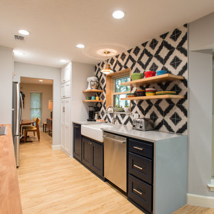 Design ideas for a mid-sized midcentury galley eat-in kitchen in Dallas with a farmhouse sink, shaker cabinets, blue cabinets, quartz benchtops, multi-coloured splashback, cement tile splashback, stainless steel appliances and vinyl floors.
