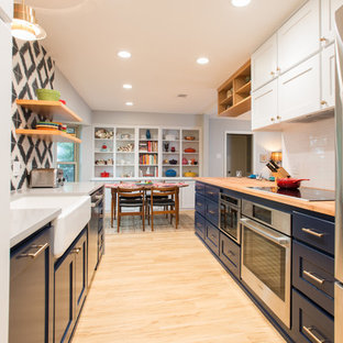 This is an example of a mid-sized midcentury galley eat-in kitchen in Dallas with a farmhouse sink, shaker cabinets, blue cabinets, quartz benchtops, multi-coloured splashback, cement tile splashback, stainless steel appliances, vinyl floors and beige floor.