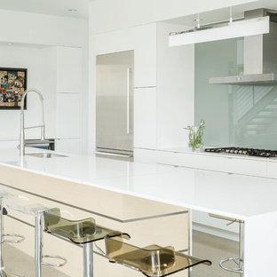 Diseño de cocina de galera, minimalista, grande, abierta, con fregadero bajoencimera, armarios con paneles lisos, puertas de armario blancas, encimera de cuarzo compacto, salpicadero de vidrio templado, electrodomésticos de acero inoxidable, una isla, salpicadero verde y suelo de cemento