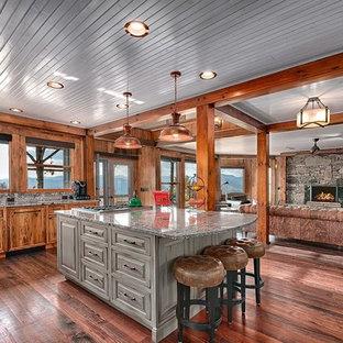 Diseño de cocina rural, abierta, con armarios con paneles empotrados, puertas de armario de madera oscura, salpicadero verde, suelo de madera oscura, una isla y suelo marrón