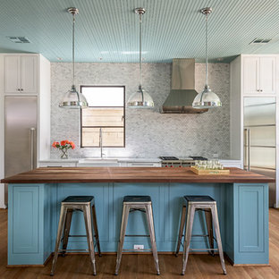 Open concept kitchen - mid-sized transitional single-wall medium tone wood floor open concept kitchen idea in Houston with a farmhouse sink, shaker cabinets, gray backsplash, mosaic tile backsplash, stainless steel appliances, an island, white cabinets and wood countertops