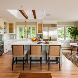 Traditional eat-in kitchen ideas - Example of a classic l-shaped light wood floor eat-in kitchen design in Boston with shaker cabinets, white cabinets, blue backsplash, subway tile backsplash, stainless steel appliances and an island
