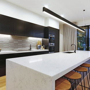 This is an example of a large contemporary galley open plan kitchen in Melbourne with an undermount sink, flat-panel cabinets, black cabinets, quartz benchtops, grey splashback, ceramic splashback, stainless steel appliances, light hardwood floors, with island, beige floor and white benchtop.