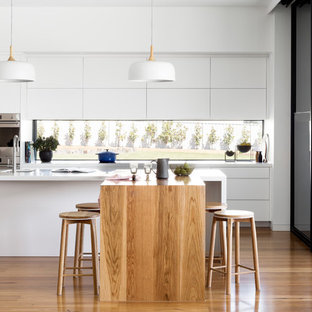 Photo of a contemporary galley kitchen in Melbourne with an undermount sink, flat-panel cabinets, white cabinets, window splashback, stainless steel appliances, medium hardwood floors, brown floor, white benchtop, quartz benchtops and multiple islands.