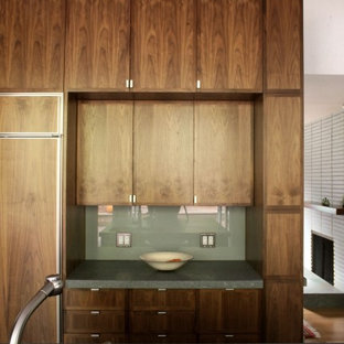 Transitional kitchen ideas - Kitchen - transitional light wood floor kitchen idea in San Francisco with flat-panel cabinets, glass sheet backsplash, paneled appliances, an undermount sink, dark wood cabinets, green backsplash and an island