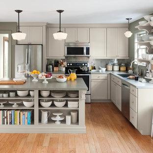 Inspiration pour une cuisine américaine rustique en L de taille moyenne avec un placard à porte shaker, des portes de placard grises, un plan de travail en surface solide, une crédence métallisée, un électroménager en acier inoxydable, un sol en bois brun et un îlot central.