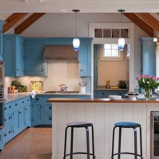 Esempio di una cucina costiera con ante in stile shaker, ante blu, paraspruzzi bianco, top in marmo, paraspruzzi con piastrelle di vetro, lavello sottopiano, elettrodomestici in acciaio inossidabile e pavimento in sughero