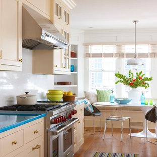 ニューヨークのビーチスタイルのおしゃれなダイニングキッチン (落し込みパネル扉のキャビネット、ベージュのキャビネット、白いキッチンパネル、ターコイズのキッチンカウンター) の写真
