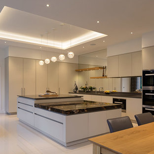 This is an example of an expansive contemporary l-shaped open plan kitchen in London with flat-panel cabinets, beige cabinets, granite worktops, metallic splashback, mirror splashback, an island, white floors, black worktops and black appliances.