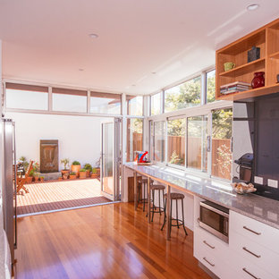 Contemporary galley eat-in kitchen in Hobart with a double-bowl sink, flat-panel cabinets, white cabinets, granite benchtops, black splashback, glass sheet splashback, stainless steel appliances, medium hardwood floors and no island.