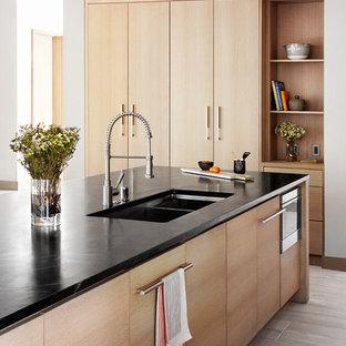 Offene, Zweizeilige Moderne Küche mit Doppelwaschbecken, flächenbündigen Schrankfronten, hellen Holzschränken, Speckstein-Arbeitsplatte, Küchengeräten aus Edelstahl, Porzellan-Bodenfliesen und Kücheninsel in Sacramento