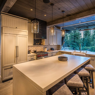 Mountain style medium tone wood floor and brown floor kitchen photo in Other with a farmhouse sink, shaker cabinets, beige cabinets, beige backsplash, paneled appliances, an island and white countertops