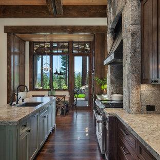 Inspiration för ett u-kök, med en undermonterad diskho, släta luckor, bruna skåp, granitbänkskiva, grått stänkskydd, stänkskydd i kalk, integrerade vitvaror, mörkt trägolv, flera köksöar och brunt golv